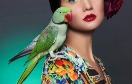 beautiful girl with a parrot and a flower in her hair.beauty young woman with colorful make-up and bird